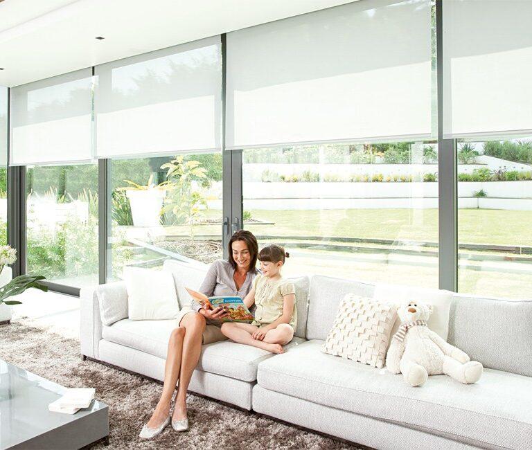 store sur des baies vitrées avec femme et petite fille sur un canapé blanc